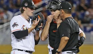 Miami Marlins pitching coach Juan Nieves, right, talks to starting pitcher Tom Koehler, left, and catcher J.T. Realmuto, center, during the first inning of a baseball game against the Houston Astros, Tuesday, May 16, 2017, in Miami. (AP Photo/Wilfredo Lee)
