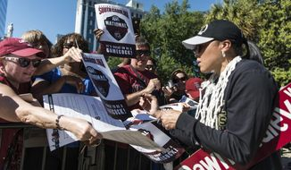 FILE - In this April 9, 2017, file photo, South Carolina coach Dawn Staley signs autographs at the conclusion of a parade for the NCAA women's basketball champions in Columbia, S.C. It's been a whirlwind month for Staley after her Gamecocks won their first national championship. There has been the WNBA draft, where she had three players taken in the first round. There's also been trips to ESPN, New York and London. (AP Photo/Sean Rayford, File)