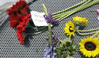 Flowers are placed on a bench at the Sound Garden sculpture, for which the band Soundgarden was named, in Seattle's Magnuson Park in tribute to Chris Cornell, Thursday, May 18, 2017. Cornell, one of the most lauded and respected contemporary lead singers in rock music with his bands Soundgarden and Audioslave, hanged himself Wednesday in a Detroit hotel room, according to the city's medical examiner. He was 52. (AP Photo/Elaine Thompson)
