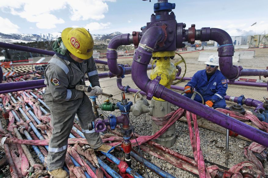 Workers tend to a well head during a hydraulic fracturing operation outside Rifle, in western Colorado on March 29, 2013. (Associated Press) **FILE**