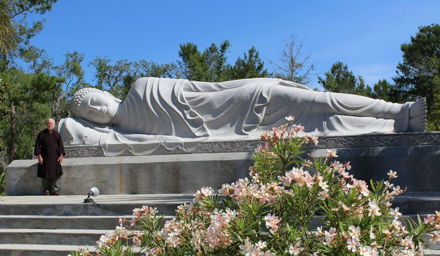 ADVANCE FOR USE SATURDAY, MAY 20 - In this May 16, 2017 photo, Ron Henderson, a staff member at the White Sands Buddhist Center, poses in Mims, Fla., stands next to the Nirvana Buddha statue. The statue is one of three massive monuments currently at the center, and weighs about 40 tons. (Jessica Saggio/Florida Today via AP)