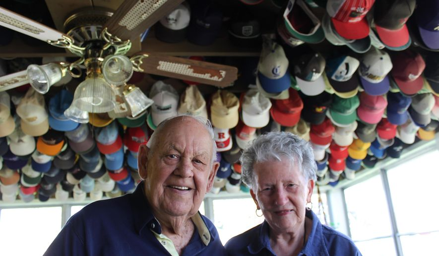 ADVANCE FOR USE SATURDAY, MAY 20, 2017 AND THEREAFTER - In this April 2017  photo, Vern and Anne Staelens stand beneath part of Vern's collection of caps. At last count Mr. Staelens, 89, has 1,738 caps, all displayed in the couple's home in Moline, Ill. (Sarah Hayden/The Dispatch via AP)