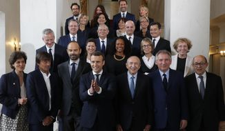 French President Emmanuel Macron, fourth left, and Prime Minister Edouard Philippe, third left, pose for a family photo after the first cabinet meeting at the Elysee Palace in Paris, Thursday, May 18, 2017. (Philippe Wojazer, Pool via AP)