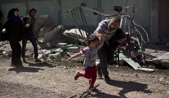 A man rushes his daughter to safety while fleeing the al-Rifai neighborhood as Iraqi special forces battle Islamic State militants, in western Mosul, Iraq, Wednesday, May 17, 2017. (AP Photo/Maya Alleruzzo)