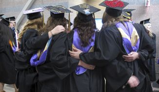 In this Saturday, May 13, 2017 photo Carroll College students pose for a photo before their graduation ceremony in Helena, Mont. With a week to go before the May 25 special congressional election, Democrat Rob Quist is hoping his outreach to college students will pay off at the ballot box. The college vote is an important part of Quist's get-out-the-vote strategy against Republican Greg Gianforte and Libertarian Mark Wicks to fill the seat vacated by Ryan Zinke when he became President Donald Trump's Interior secretary. (AP Photo/Matt Volz)