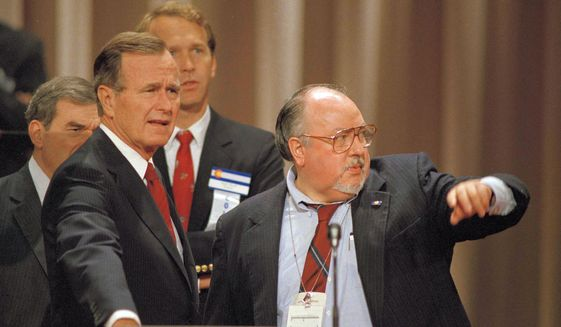 In this Aug. 17, 1988 file photo, Vice President George H.W. Bush, left, gets some advice from his media advisor, Roger Ailes, right, as they stand behind the podium at the Superdome in New Orleans, La., prior to the start of the Republican National Convention.  Fox News said on Thursday, May 18, 2017, that Ailes has died. He was 77. (AP Photo/Ron Edmonds)