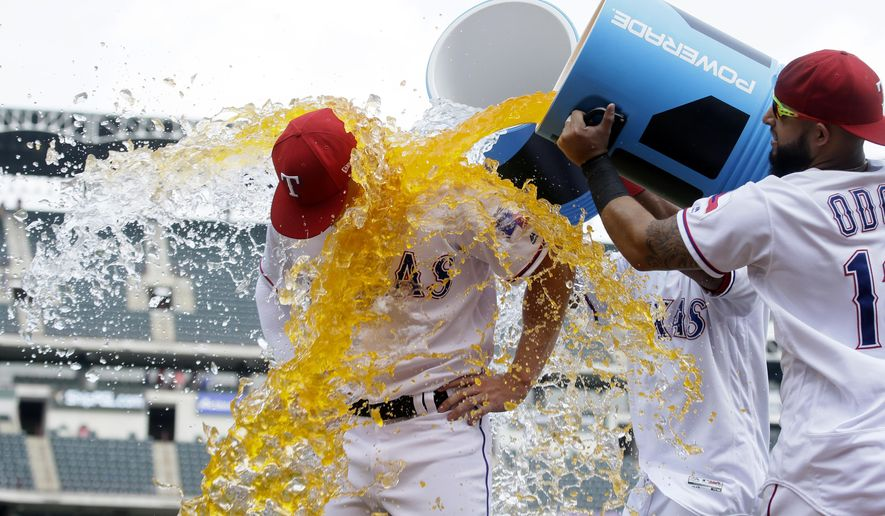 Texas Rangers Ryan Rua, left, is dunked with drink coolers by teammates Rougned Odor, right, and Elvis Andrus after a baseball game against the Philadelphia Phillies in Arlington,Texas, Thursday, May 18, 2017. The Rangers won 8-4. (AP Photo/LM Otero)