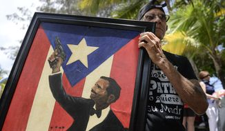 A supporter of Puerto Rican nationalist Oscar Lopez Rivera holds a painting of late nationalist leader Pedro Albizua Campos as Lopez arrives to give a press conference following his release from house arrest after decades in custody, on El Escambron Beach in San Juan, Puerto Rico, Wednesday, May 17, 2017. Lopez was considered a top leader of the Armed Forces of National Liberation, or FALN, an ultranationalist Puerto Rican group that claimed responsibility for more than 100 bombings at government buildings, department stores, banks and restaurants in New York, Chicago, Washington and Puerto Rico during the 1970s and early 1980s. (AP Photo/Carlos Giusti) PUERTO RICO OUT - NO PUBLICAR EN PUERTO RICO