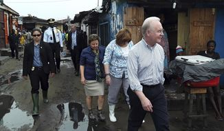 US Secretary of Health and Human Services Tom Price, right, walks Thursday May 18, 2017 through a densely-populated and heavily congested Monrovia, Liberia, slum community which was quarantined in 2014 when Ebola struck there killing dozens. This is Price's first visit outside the US since assuming the position. (AP Photo/Jonathan Paye-Layleh)