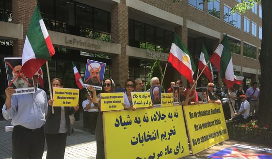 Protestors shout slogans and hold signs against Iranian elections outside the Special Interest Section of the Iranian Embassy in Washington D.C. on Friday. (Laura Kelly)