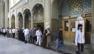 Iranian voters line up at a polling station for the presidential and municipal council election in the city of Qom, 78 miles (125 kilometers) south of the capital Tehran, Iran, Friday, May 19, 2017. Iranians began voting Friday in the country's first presidential election since its nuclear deal with world powers, as incumbent Hassan Rouhani faced a staunch challenge from a hard-line opponent over his outreach to the wider world. (AP Photo/Ebrahim Noroozi)