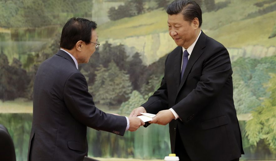 South Korean special envoy Lee Hae-chan, left, passes on a hand-written letter from South Korean President Moon Jae-in to Chinese President Xi Jinping during a meeting at the Great Hall of the People in Beijing, Friday, May 19, 2017. A senior foreign policy adviser to Chinese President Xi stressed the importance of relations with South Korea on Friday as the two countries attempt to mend a rift in ties over the deployment of a U.S. missile-defense system to guard against North Korean threats. (Jason Lee/Pool Photo via AP)
