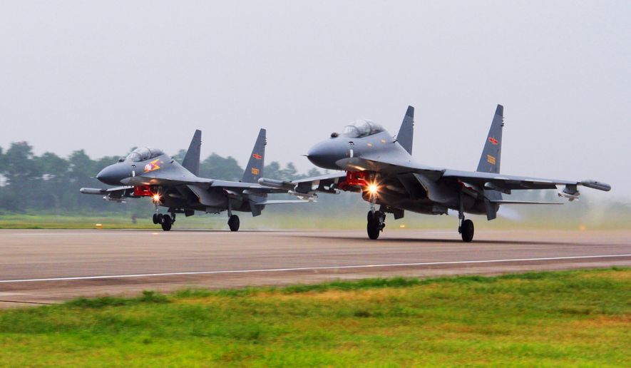 In this undated file photo released Saturday, Aug. 6, 2016, by China's Xinhua News Agency, two Chinese SU-30 fighter jets take off from an unspecified location to fly a patrol over the South China Sea. (Jin Danhua/Xinhua via AP) ** FILE **