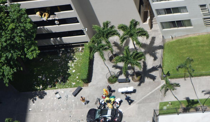 In this photo provided by Tracy Hino, a car lies damaged after a woman apparently drove her car off the third floor of a residential parking structure and landed in a common area of Kukui Tower near the city's Chinatown neighborhood, Friday, May 19, 2017, in Honolulu. Police tells the Star-Advertiser that the woman was taken to the Queen's Medical Center in critical condition. (Tracy Hino via AP)