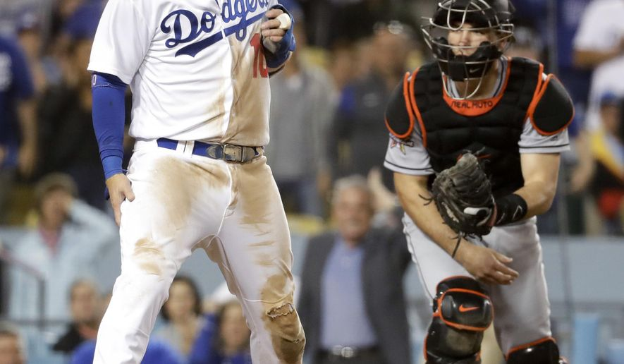 Los Angeles Dodgers' Justin Turner holds his leg after getting being tagged out by Miami Marlins catcher J.T. Realmuto during the seventh inning of a baseball game in Los Angeles, Thursday, May 18, 2017. Turner limped off the field and left the game. (AP Photo/Chris Carlson)