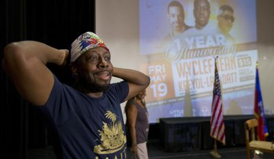 In this, Friday, May 19, 2017 photo, Haitian-American hip-hop star Wyclef Jean uses a small Haitian flag as a bandana as he prepares to speak during a news conference at the Little Haiti Cultural Center in Miami. Jean performs Friday in Miami's Little Haiti, a community worried that the Trump Administration won't renew post-earthquake immigration benefits for roughly 50,000 Haitians. (AP Photo/Wilfredo Lee)