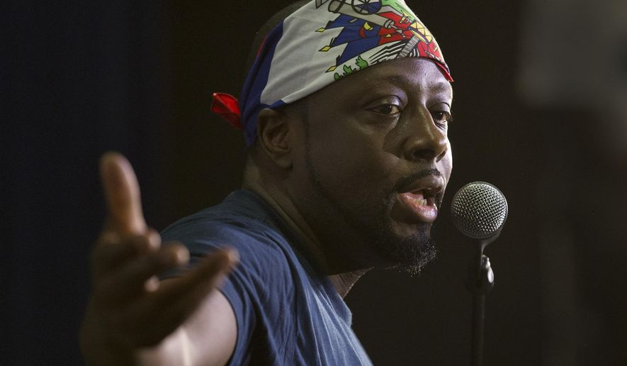 In this, Friday, May 19, 2017 photo, Haitian-American hip-hop star Wyclef Jean gestures as he speaks during a news conference at the Little Haiti Cultural Center in Miami. Jean performs Friday in Miami's Little Haiti, a community worried that the Trump Administration won't renew post-earthquake immigration benefits for roughly 50,000 Haitians. (AP Photo/Wilfredo Lee)