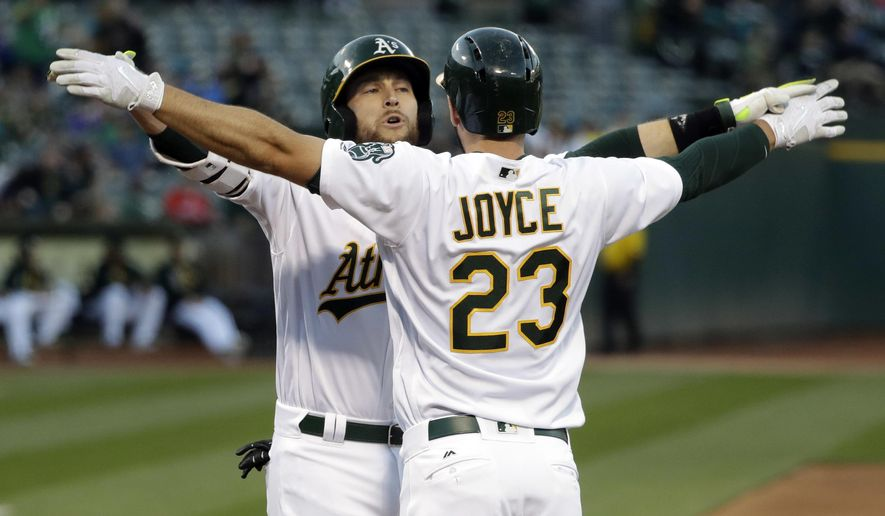 Oakland Athletics' Jed Lowrie, left, celebrates his two-run home run at the plate with teammate Matt Joyce (23) during the first inning of a baseball game Thursday, May 18, 2017, in Oakland, Calif. (AP Photo/Marcio Jose Sanchez)