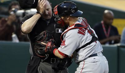 Home plate umpire Marty Foster, left, holds his head next to Boston Red Sox catcher Christian Vazquez after Foster was hit by a pitch during the third inning of the Red Sox's baseball game against the Oakland Athletics on Thursday, May 18, 2017, in Oakland, Calif. (AP Photo/Marcio Jose Sanchez)