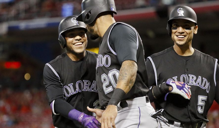 Colorado Rockies' Alexi Amarista, left, celebrates with Ian Desmond (20) and Carlos Gonzalez (5) after hitting a three-run home run off Cincinnati Reds starting pitcher Lisalverto Bonilla during the sixth inning of a baseball game, Friday, May 19, 2017, in Cincinnati. (AP Photo/John Minchillo)