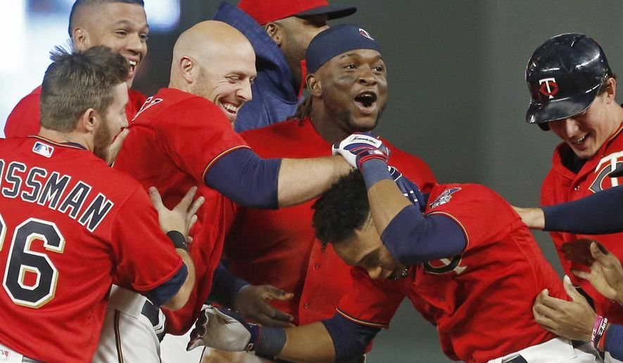Minnesota Twins' Jorge Polanco, right, is swarmed by teammates after his walk-off sacrifice fly in the 10th inning of a baseball game against the Kansas City Royals on Friday, May 19, 2017, in Minneapolis. The Twins won 4-3. (AP Photo/Jim Mone)