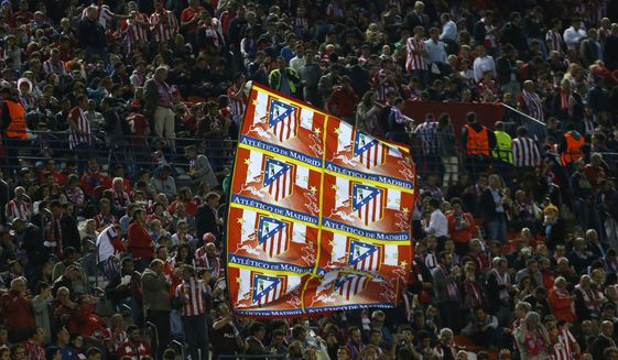 In this photo taken on Wednesday, May 10, 2017, an Atletico Madrid supporter waves a team flag during the Champions League semifinal second leg soccer match between Atletico Madrid and Real Madrid at the Vicente Calderon stadium in Madrid. Atletico Madrid is bidding farewell to its beloved Vicente Calderon. The Spanish league game against Athletic Bilbao on Sunday will be Atletico's last at the old-fashioned venue. The stadium will still host the Copa del Rey final between Barcelona and Alaves on May 27.(AP Photo/Francisco Seco)