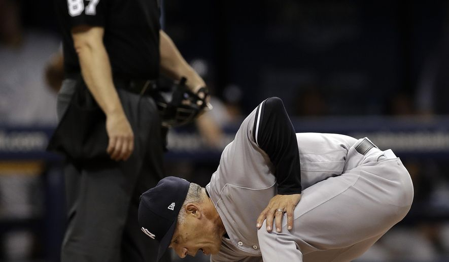New York Yankees manager Joe Girardi covers home plate with dirt after being ejected along with pitching coach Larry Rothschild by home plate umpire Scott Barry during the fifth inning of a baseball game against the Tampa Bay Rays, Saturday, May 20, 2017, in St. Petersburg, Fla. (AP Photo/Chris O'Meara)