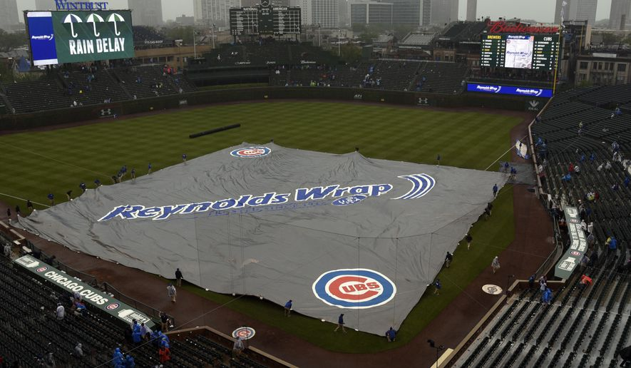A tarp covers the field during a rain delay in the sixth inning of a baseball game between the Chicago Cubs and the Milwaukee Brewers, Friday, May, 19, 2017, in Chicago. (AP Photo/David Banks)
