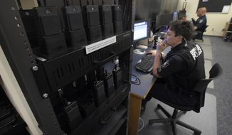ADVANCE FOR WEEKEND EDITIONS - In this Wednesday May 3, 2017, photo, body cameras sit on chargers while Officer Karin Stauder and Officer Luther MacLean work on reports in the report room of the Corvallis Police Department in Oregon. For nearly a year, 55 body-worn cameras have been sitting in charging docks in the Law Enforcement Center in Corvallis. (Andy Cripe/The Corvallis Gazette-Times via AP)