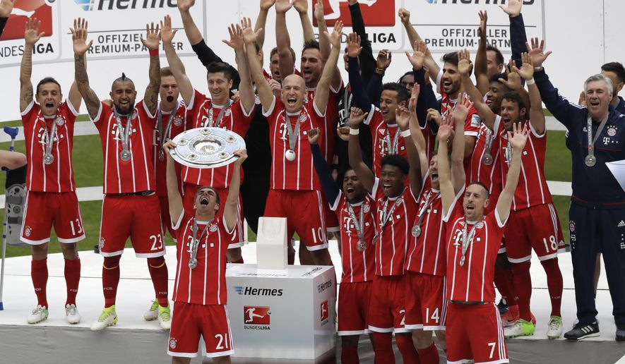 Bayern's Philipp Lahm lifts the trophy as his team celebrate winning the Bundesliga title after the German first division Bundesliga soccer match between FC Bayern Munich and SC Freiburg at the Allianz Arena stadium in Munich, Germany, Saturday, May 20, 2017. (AP Photo/Matthias Schrader)