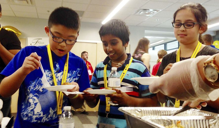 In this May 18, 2017 photo, Eric Zheng, left, Rohith Pallamreddy and Sophia Ullman, right, sample a Korean BBQ chicken meal at the Fulton County Schools Administrative Center, in Atlanta. The 4th graders participated in a taste test event that school district officials started last year to promote healthier menu items that stick to federal regulations under review by the Trump administration. (AP Photo/ Kathleen Foody)