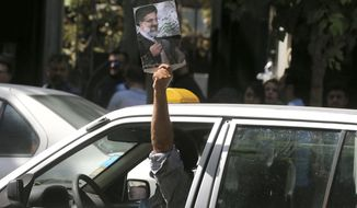 A supporter holds a poster of Iranian presidential candidate cleric Ebrahim Raisi, the main challenger of President Hassan Rouhani, outside a polling station for the presidential and municipal councils election, in Tehran, Iran, Friday, May 19, 2017. Millions of Iranians voted late into the night Friday to decide whether incumbent President Hassan Rouhani deserves another four years in office after securing a landmark nuclear deal, or if the sluggish economy demands a new hard-line leader who could return the country to a more confrontational path with the West. (AP Photo/Vahid Salemi)