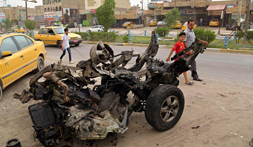Civilians pass a destroyed car in the a car bomb explosion in southwestern Baghdad, Iraq, Saturday, May 20, 2017. Two car bombs in southwestern Baghdad killed and wounded people and police officers late on Friday night according to Iraqi police and hospital officials. (AP Photo/Karim Kadim)