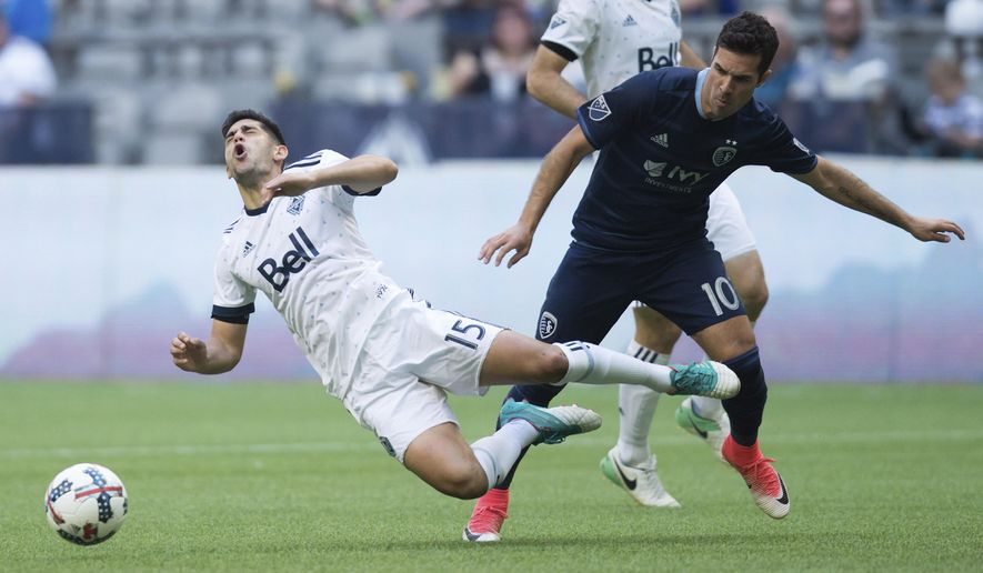 Vancouver Whitecaps' Matias Laba, left, is upended by Sporting Kansas City's Benny Feilhaber during the second half of an MLS soccer game in Vancouver, British Columbia, on Saturday May 20, 2017. (Darryl Dyck/The Canadian Press via AP)