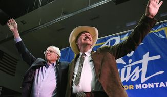 Sen. Bernie Sanders, left, and Rob Quist wave to the crowd after the conclusion of Sanders' speech on Saturday, May 20, 2017, at the Adams Center on the University of Montana campus, in Missoula, Mont. (Tommy Martino /The Missoulian via AP)