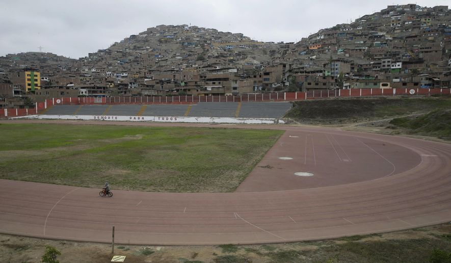In this May 14, 2017 photo, a child rides his bicycle inside a venue that will host baseball, softball, archery and other sports during the 2019 Pan American Games in Lima, Peru. The quadrennial event, which will attract athletes from Alaska to Argentina, has no sponsors, no marketing and is relying on Peru's national government. (AP Photo/Martin Mejia)
