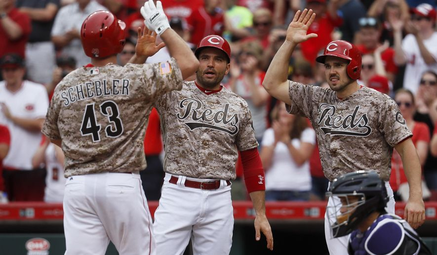 Cincinnati Reds' Scott Schebler (43) celebrates with Joey Votto, center, and Adam Duvall, right, after hitting the go-ahead three-run home run off Colorado Rockies relief pitcher Mike Dunn in the sixth inning of a baseball game, Saturday, May 20, 2017, in Cincinnati. (AP Photo/John Minchillo)