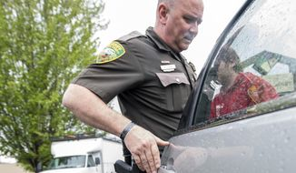 In this May 11, 2017 photo, Deputy Kevin Dickey, a compliance officer with the Lewis County Drug Court, lets a man he noted who has mental health issues out of the back of the car so the man could go inside and withdraw cash from a bank in Centralia, Wash. (Pete Caster/The Chronicle via AP)