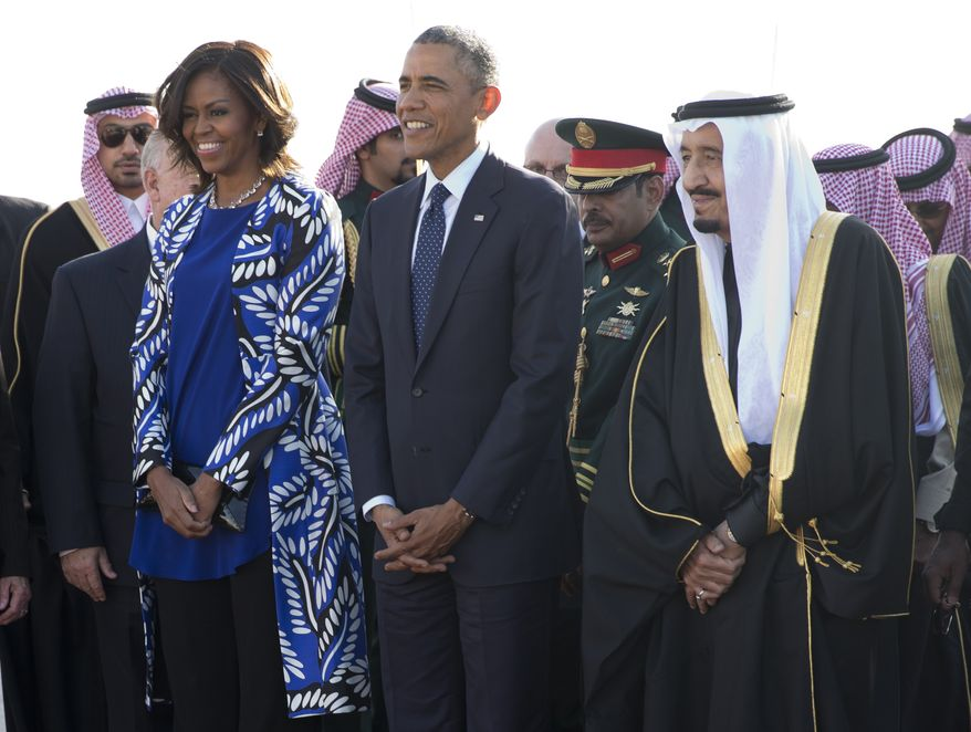 FILE - In this Jan. 27, 2015 file photo, President Barack Obama and first lady Michelle Obama stand with new Saudi King Salman bin Abdul Aziz they arrive on Air Force One at King Khalid International Airport, in Riyadh, Saudi Arabia. Ignoring President Donald Trump's past admonition, U.S. first lady Melania Trump did not cover her head Saturday when they arrived in Saudi Arabia on the opening leg of his first international tour since taking office. Two years ago, then-citizen Trump criticized then-first lady Michelle Obama's decision to go bare-headed on a January 2015 visit with her husband. (AP Photo/Carolyn Kaster)