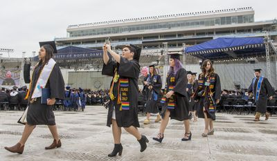 Notre Dame graduates walk out of Notre Dame Stadium in protest as Vice President Mike Pence speaks at the 2017 commencement ceremony Sunday, May 21, 2017, in South Bend, Ind. (Robert Franklin/South Bend Tribune via AP)