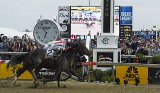 Cloud Computing (2), ridden by Javier Castellano, wins the 142nd Preakness Stakes horse race at Pimlico race course as Classic Empire with Julien Leparoux aboard takes second, Saturday, May 20, 2017, in Baltimore. NFL football player Baltimore Ravens first-round draft pick Marlon Humphrey, far left, cheers the finish. (AP Photo/Mike Stewart) **FILE**
