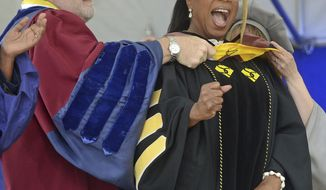 Bill E. Peterson, Associate Provost and Dean of Academic Development, left,  presents Oprah Winfrey with an honorary degree during Smith College's 139th Commencement ceremony on Sunday, May 21, 2017 in Northampton, Mass. The author, actress, philanthropist and former talk show host gave the college's commencement address. (David Molnar/Springfield Republican via AP)