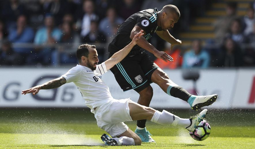 West Bromwich Albion's Salomon Rondon, right, is tackled by Swansea City's Leon Britton during their English Premier League soccer match at the Liberty Stadium, Swansea, England, Sunday May 21, 2017. (David Davies/PA via AP)