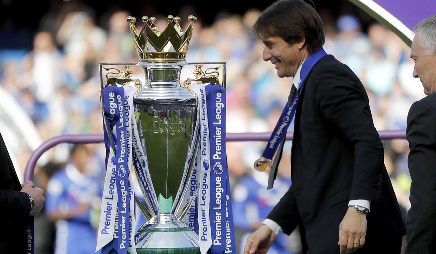 Chelsea's manager Antonio Conte walks past the trophy with his winner's medal after the English Premier League soccer match between Chelsea and Sunderland at Stamford Bridge stadium in London, Sunday, May 21, 2017. (AP Photo/Frank Augstein)