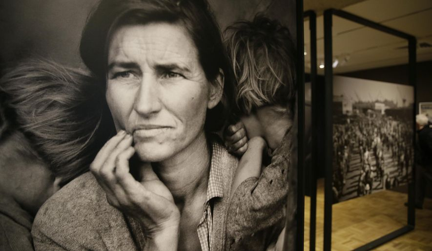 "In this photo taken Thursday, May 11, 2017, the iconic photograph Migrant Mother looks out at the exhibit ""Dorothea Lange: Politics of Seeing,"" at the Oakland Museum of California in Oakland, Calif. The three major themes of the Lange display are the Great Depression, the home front during World War II and the urban decline and postwar sprawl in California. Running through August 13, the exhibit includes 100 of Lange's photographs, including recognized works as well as new, improved unframed prints that have been digitally scanned. (AP Photo/Eric Risberg)"