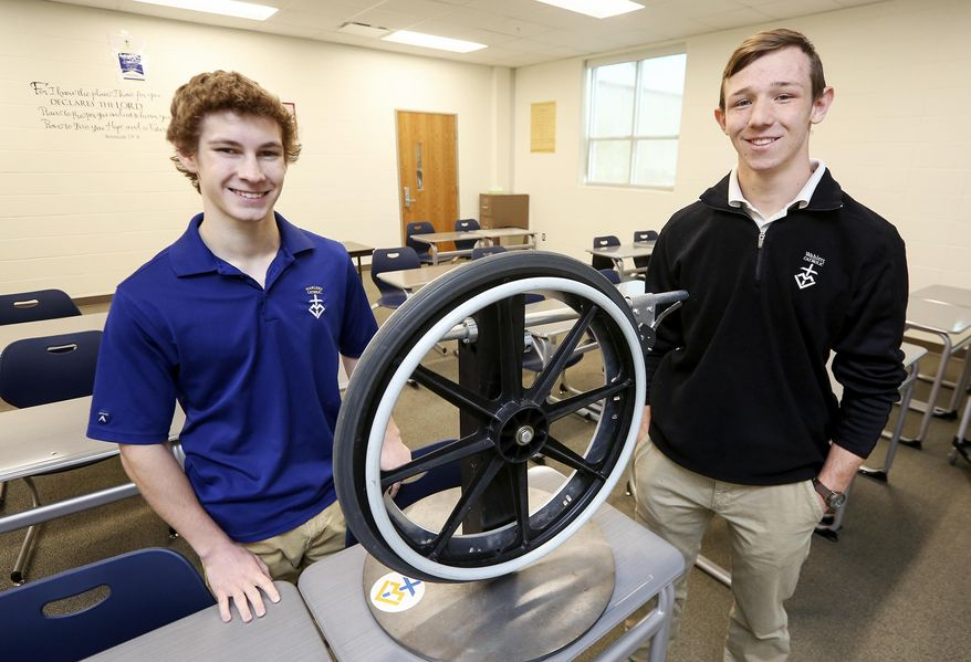 In this Monday, April 24, 2017 photo, Wahlert Catholic High School seniors Tony Ward, left,  and Grant Oberfoell, who helped to create the Feltes One Way, pose with it at Wahlert Catholic High School in Dubuque, Iowa. (Nicki Kohl /Telegraph Herald via AP)