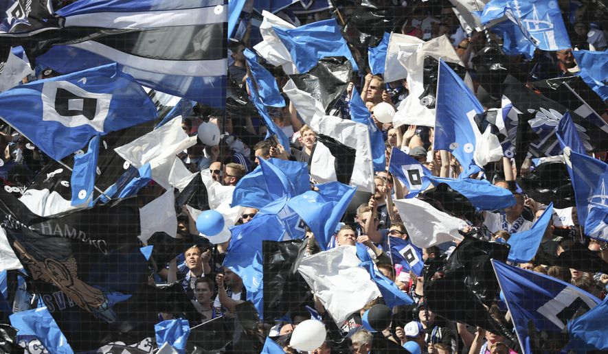 Hamburg fans wave flags during the German Bundesliga soccer match between Hamburger SV and VfL Wolfsburg in Hamburg, Germany, saturday, May 20, 2017. Luca Waldschmidt scored one day after his 21st birthday for Hamburger SV to clinch Bundesliga survival with a late 2-1 win over Wolfsburg on the final day of the season Saturday.  (Christian Charisius/dpa via AP)