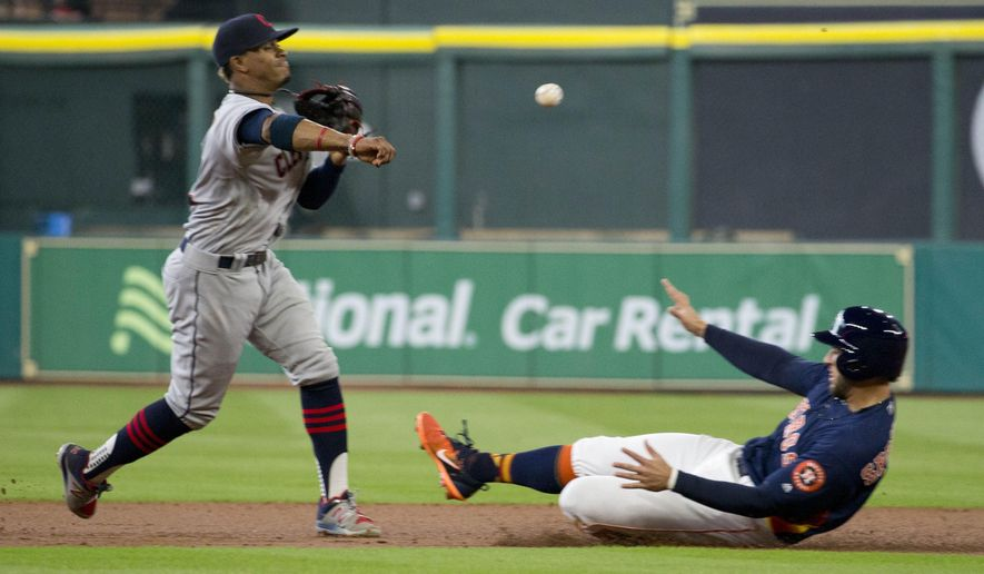 Cleveland Indians shortstop Francisco Lindor, left, makes the double-play throw to first as Houston Astros' George Springer is out at second base in the first inning of a baseball game Sunday, May 21, 2017, in Houston. (AP Photo/Richard Carson)