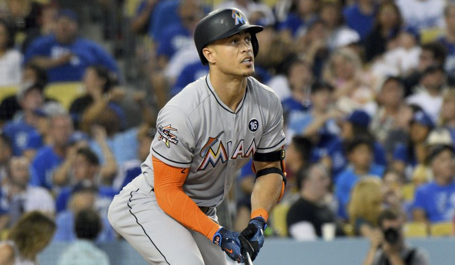 Miami Marlins' Giancarlo Stanton watches the flight of his double against the Los Angeles Dodgers in the third inning of a baseball game in Los Angeles, Saturday, May 20, 2017. Stanton's double scored Marcell Ozuna. (AP Photo/Michael Owen Baker)