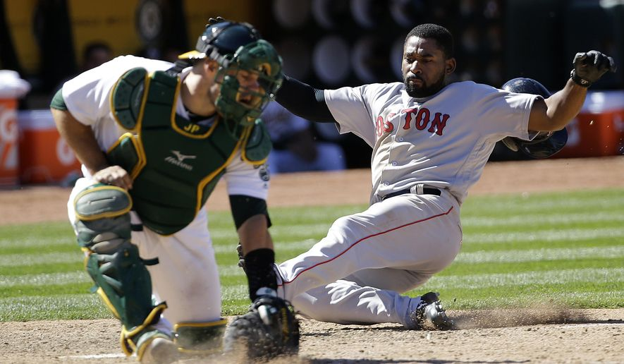 Boston Red Sox's Jackie Bradley Jr., right, scores against Oakland Athletics catcher Josh Phegley during the ninth inning of a baseball game in Oakland, Calif., Sunday, May 21, 2017. (AP Photo/Jeff Chiu)